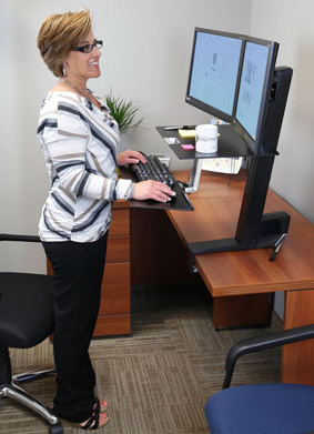 Photo of a woman at a standing workstation