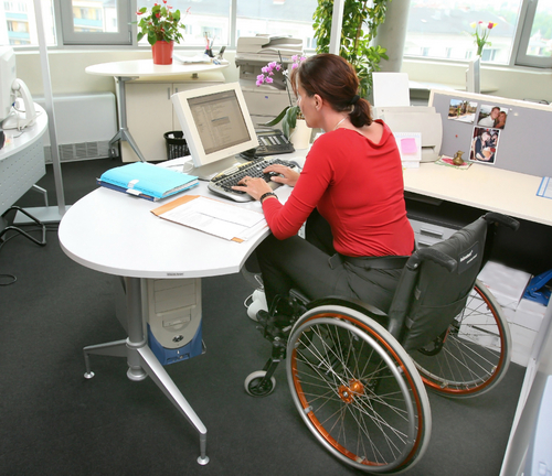 Photo of a woman in a wheelchair working at her desk