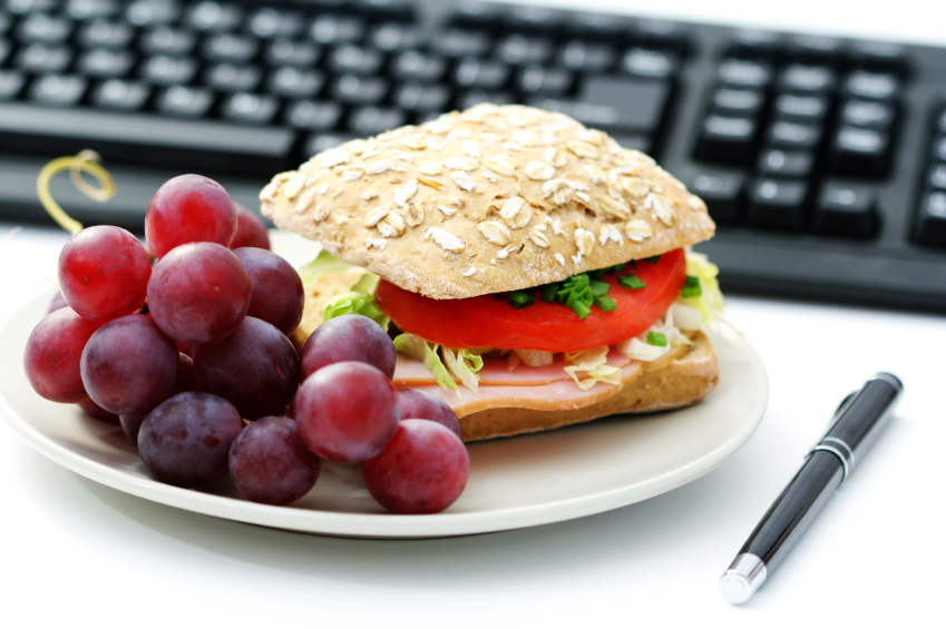 Photo of sandwich and grapes on workplace desk